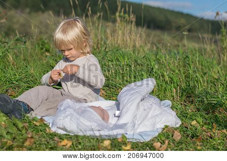 A blond boy with younger newborn brother siiting on a grass during outing