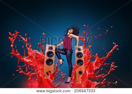 Happy young woman listening music with loud speakers in front of liquid splash explosion background