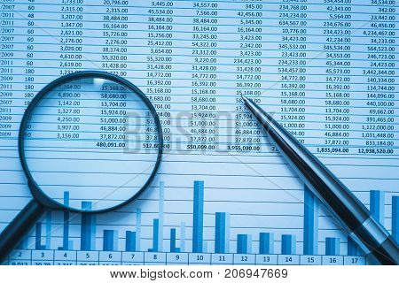 Spreadsheet bank accounts accounting finance forensics with magnifying glass and pen. Concept for financial fraud investigation audit and analysis.
