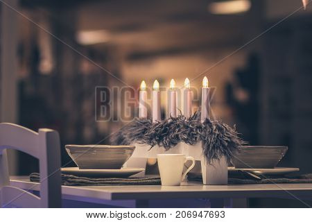 Christmas dinner table for two. Cozy warm table set with candles. Perfect romantic atmosphere. Concept for love holidays celebration.