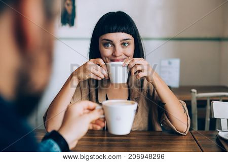 Happy romantic couple on date drink warm coffee with milk she looks lovingly at her boyfriend or partner smiles and spark in her eyes. early morning family routine