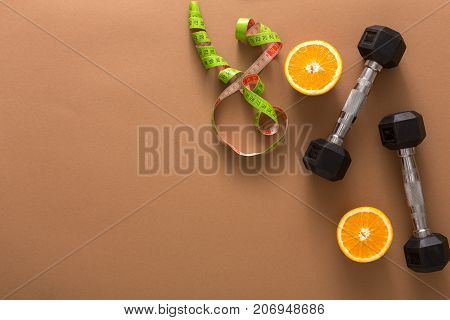 Fitness background. Workout plan and slimming tools copy space. Dumbbells, measuring tape and grapefruit on brown backdrop