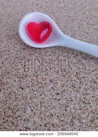 Mini heart jelly in white little spoon on plywood