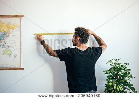 Young attractive middle aged man with curly hair and tattoo arms uses measuring tape to find out length and height of wall next to world map moves to new home or apartment