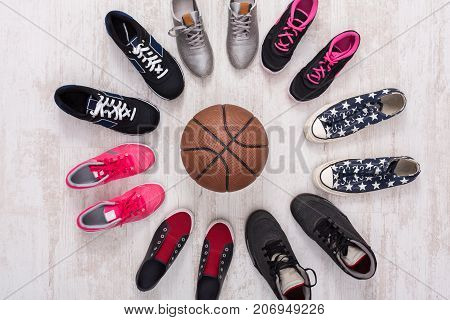 Bright and colorful sport shoes circle with basket ball top view. Set of different sneakers on wooden floor, copy space. Team game, competition concept