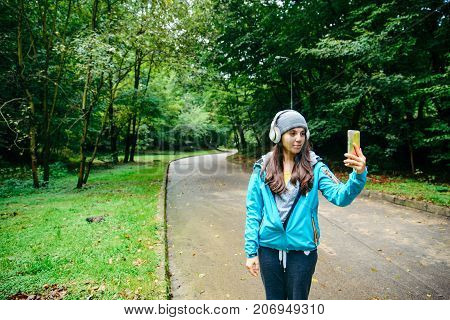young pretty woman was interrupted video call while run in the park young autumn day