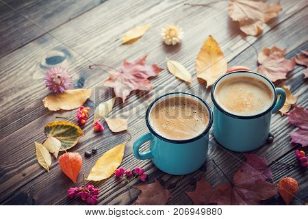 Coffee In Blue Enameled Cups And Autumn Leaves On Wooden Desk. Retro Toned.