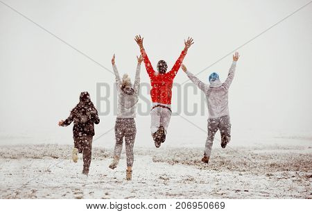 Happy friends is having fun and enjoying first snow. Group of people run and jump. Winter's beginning concept