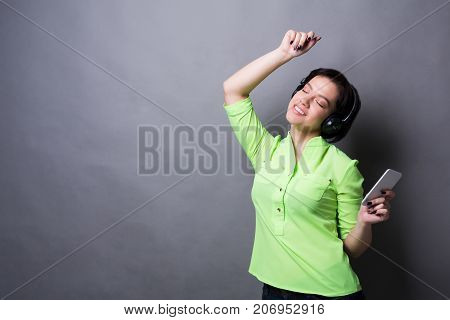 Lovely melody. Woman listen to music in earphones with closed eyes, standing on gray studio background