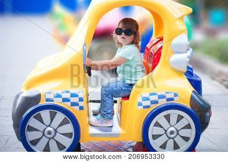 Toddler kid ride electric taxi car attraction having fun at summer day lifestyle. Theme park for children vacation.