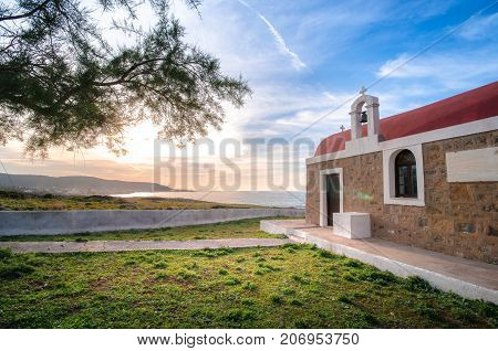 Amazing pictorial view of an old stone church beside blue sea, at sunset, Milatos, Crete, Greece.