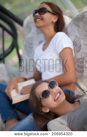 Best friends spending tine together in summer day. Wearing sunglasses smilimg reading. Doing homework lerning.