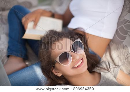 Best friends spending time together in summer day. Wearing sunglasses smiling reading. Doing homework lerning. Young attractive girls.