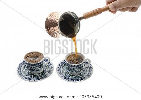 Pouring Turkish coffee in cup isolated on white background.