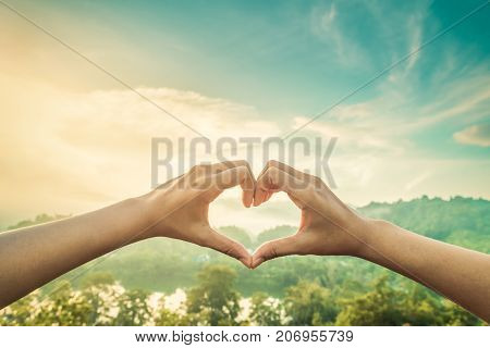 Female hands in the form of heart against sunlight with mist in blue sky Hands in shape of love heart - Love concept.