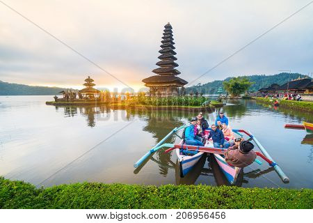 Bali Indonesia-August 12 2017: The tourist sit in the traditional boat at Beratan lake and take photo with enjoy view Pura Ulun Danu Bratan temple in sunrise sky The most famous tourist attraction in Indonesia.