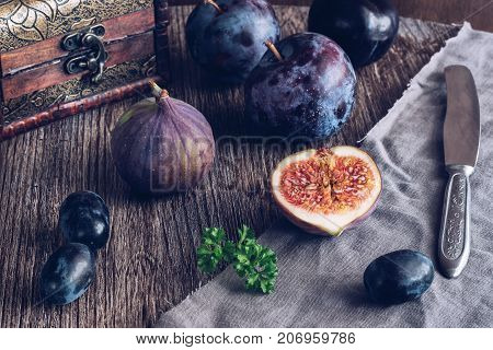 The fig is cut on a wooden table with grapes and plums. Still life with figs. Selective focus.