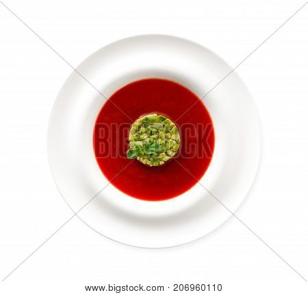 Delicious tasty cold tomato soup gazpacho with avocado isolated on white background. Portion of traditional Spanish red vegetable broth, restaurant serving