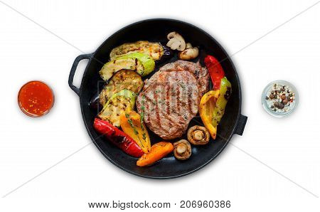 Grilled beef steak and roasted vegetables isolated on white background. Juicy meat dish with sauce, rosemary, peppers and cutlery in fry pan. Restaurant food