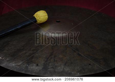 Cymbal con mallet gialla e nera con luce poco diffusa, scura