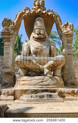The Lakshmi Narasimha statue is the largest monolith statue in Hampi, Karnataka, India. The god is sitting in a cross-legged Yoga position on the coil of a giant seven-headed snake called Sesha.