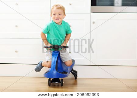 Happy little boy having fun and driving toy race car at home
