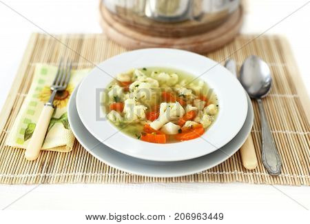 Broth soup with noodle and vegetables on table