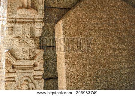Hampi, India - November 20, 2012: Details of religious inscriptions on the walls of Prasanna Virupaksha temple is also known as the Underground Shiva Temple in Hampi, Karnataka, India.