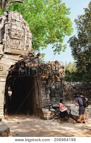 Siem Reap, Cambodia - February 4, 2016: Eastern gopuram of Ta Som Temple in Angkor Complex, Siem Reap, Cambodia. A small Cambodian girl sells souvenirs to tourists at the temple walls