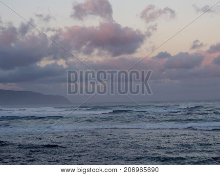 Beautiful pink and purple Dawn over the ocean with waves rolling towards the shore on the North Shore of Oahu.