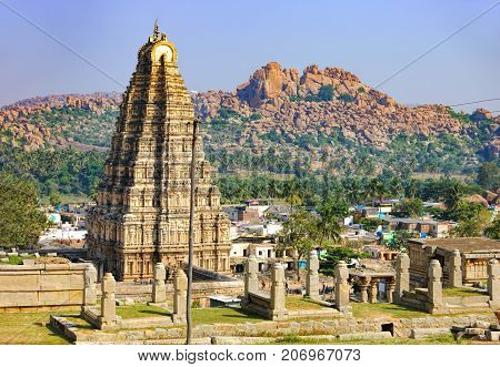 Virupaksha Temple located in the ruins of ancient city Vijayanagar at Hampi, India. Landscape with unique mountain formation tropical nature on the horizon and old hindu temple.