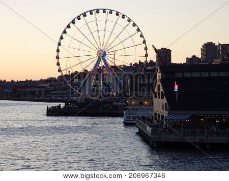 Downtown Seattle Washington USA - June 25 2016 - Night scene in the Waterfront Park with Ferris Wheel with LED lights on in the background.