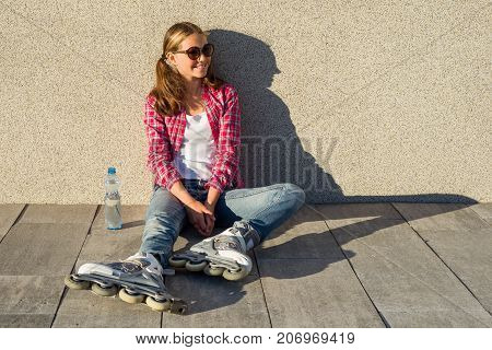 Young smiling cool girl shod in rollerblades sits on the sidewalk and holding a water bottle. Sports health and active leisure.