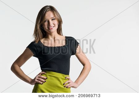 Beautiful young woman is holding hands on hip laughing and looking at camera. Studio shot on white background.