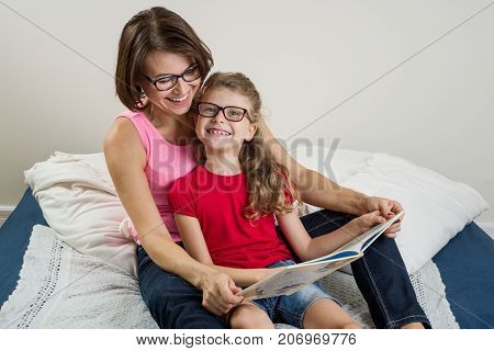 Happy woman with her daughter child reading together a book at home. Mom and daughter wearing glasses.