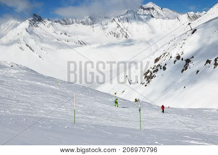 Skier And Snowboarder Downhill On Freeride Trace And Mountains In Clouds