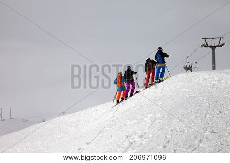 Skiers Before Downhill On Off-piste Slope And Overcast Misty Sky
