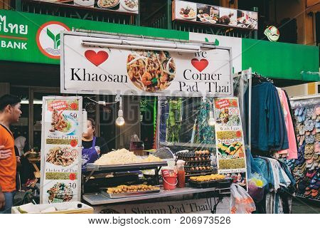 Bangkok, Thailand - January 31, 2016: Thai street vendor selling Pad Thai - traditional food on Khaosan road famous district for back packer and budget tourist. Sign with inscription Khaosan road.