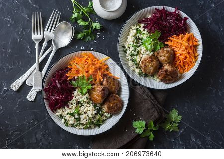 Fall buddha bowl. Bulgur spinach meatballs beets carrots - balanced healthy eating lunch. On a dark background top view. Comfort autumn winter food