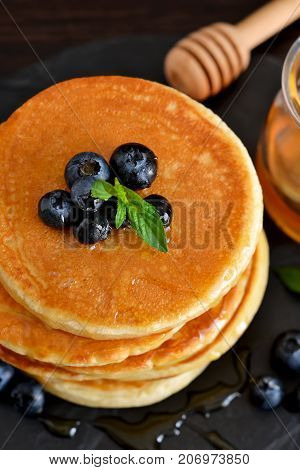 Homemade oat pancakes with honey and blueberries for breakfast on a stone plate. Good morning!