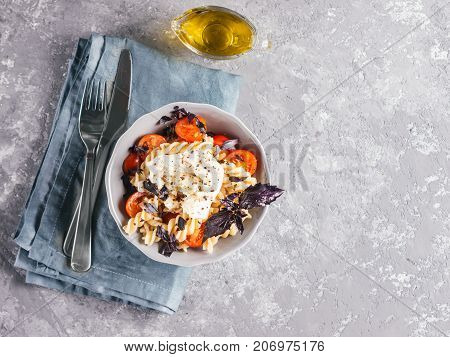 Tasty italian fusilli pasta with cherry, mozarella or buratta cheese and fresh basil. Dish with pasta on gray concrete background. Top view. Copy space. Healthy food concept and recipe idea.