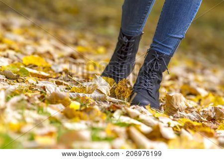 woman feet boots walking on fall leaves outdoor with autumn season nature on background