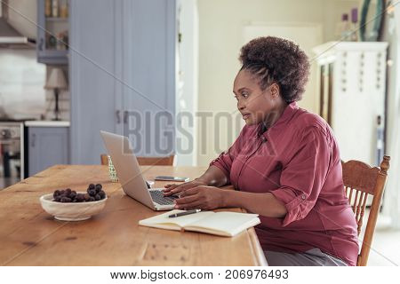 Smiling young African woman sitting alone at her kitchen table while working online from home with a laptop