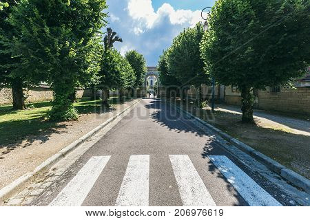pedestrian crossing on a narrow street in a small town. In the distance you can see the entrance to the monastery