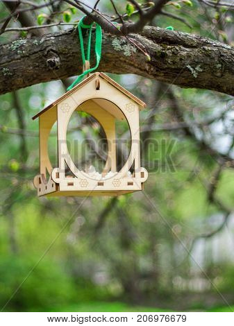 Wooden feeder for birds in the city park