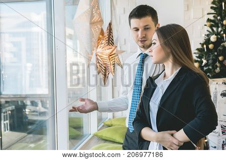 girl in suit looks out the window, man shows woman the view from the window, office