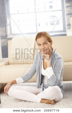 hübsch junge Frau sitzen auf Boden in hellen Wohnzimmer, Lächeln in die Kamera.?