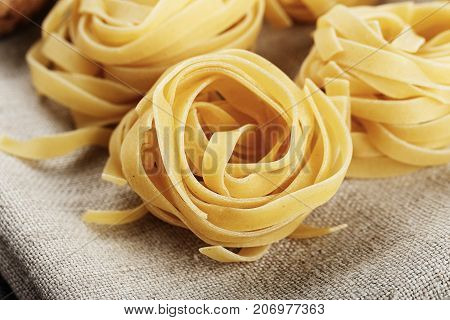 raw italian tagliatelle paste on a linen napkin close-up