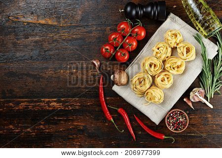 raw tagliatelle with tomatoes pepper and olive oil on a wooden background top view space for text