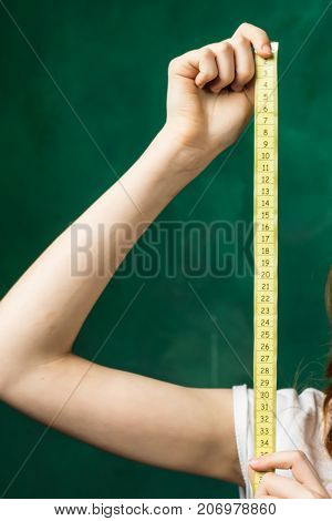 hand holding a centimeter tape close-up on a green background, isolated